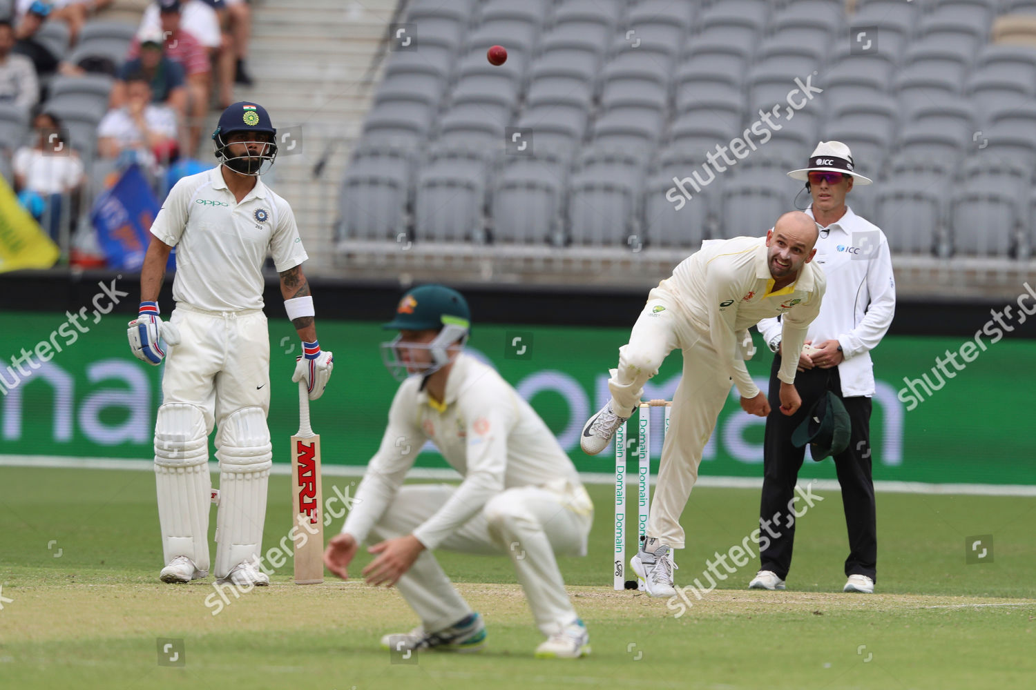 Australias Nathan Lyon bowls watched by Indias Editorial