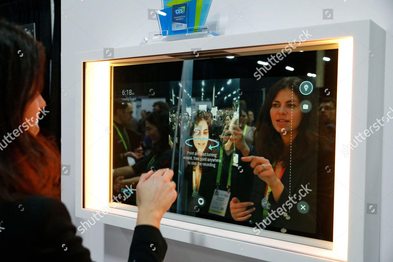 woman demonstrates Artemis smart mirror CareOS booth Editorial Stock