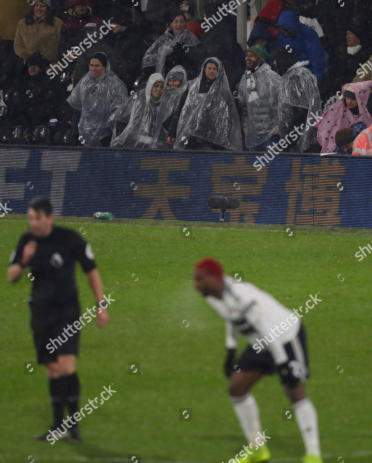 Fulham fans wearing rain ponchos Editorial Stock Photo