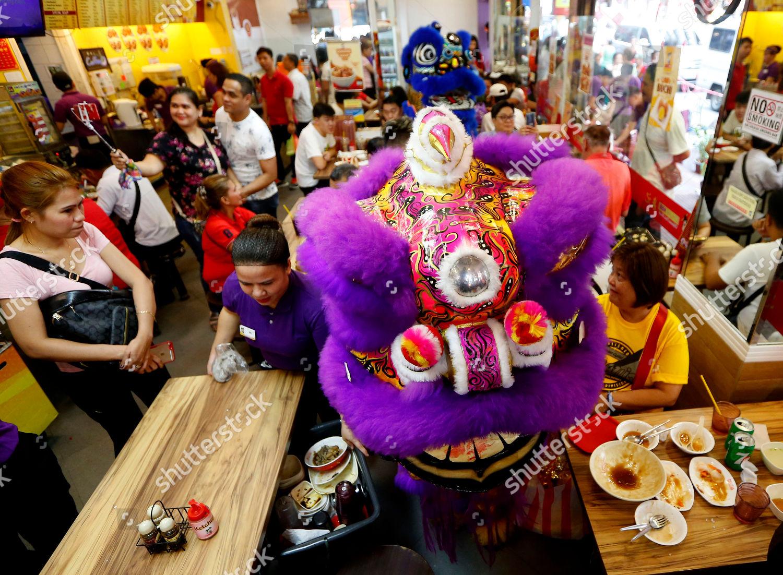 Lion dancers perform before customers inside restaurant