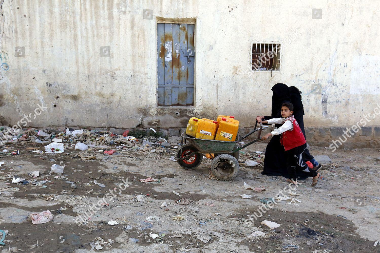 Yemeni boy his sister push wheelbarrow empty Editorial Stock