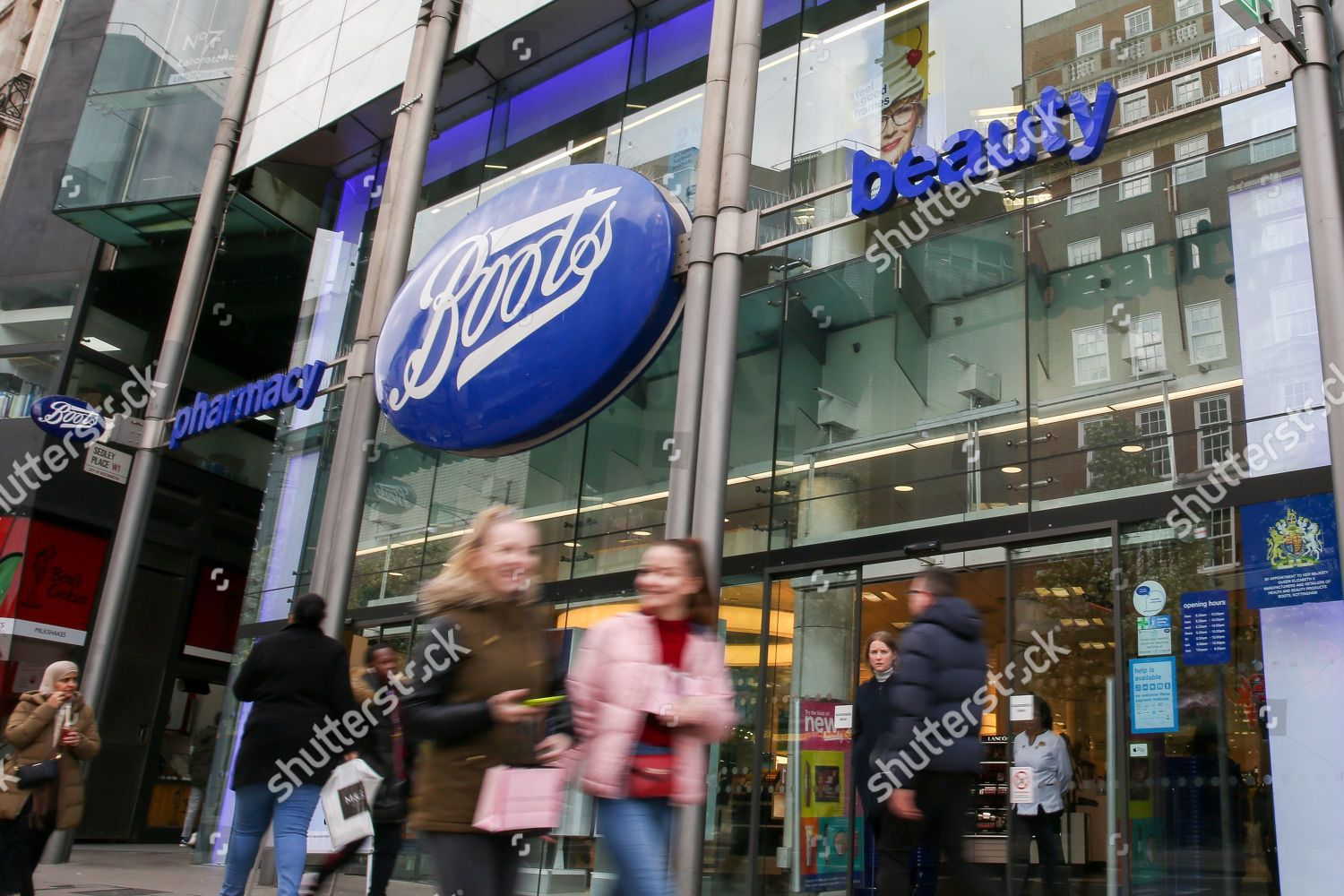 Shoppers walk past Boots store on Oxford Editorial Stock