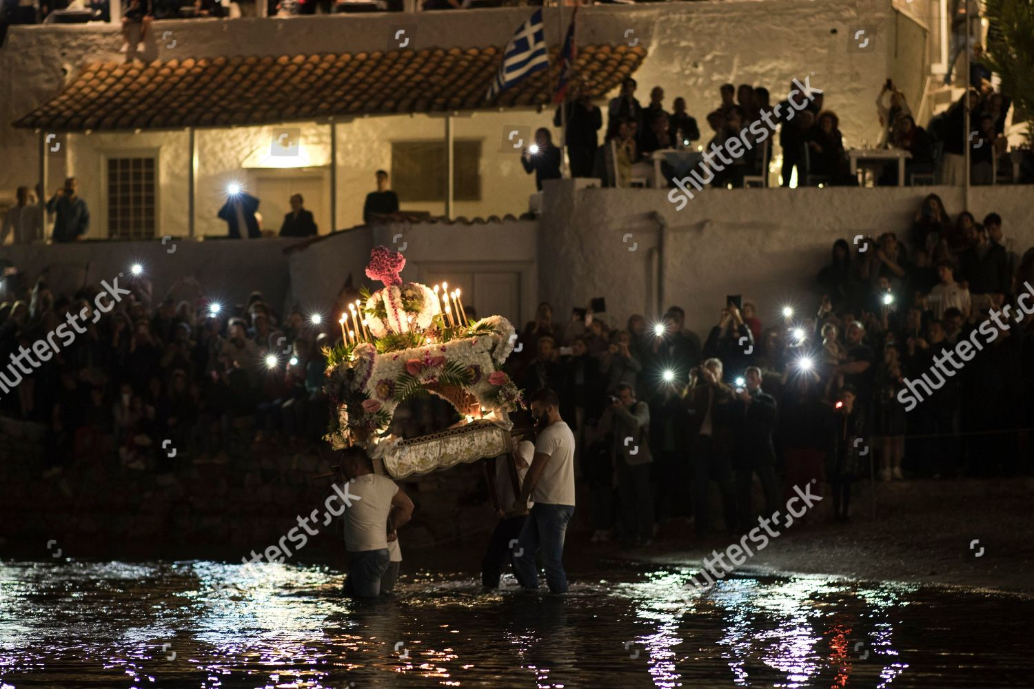 Orthodox faithful hold bier into sea during Editorial Stock