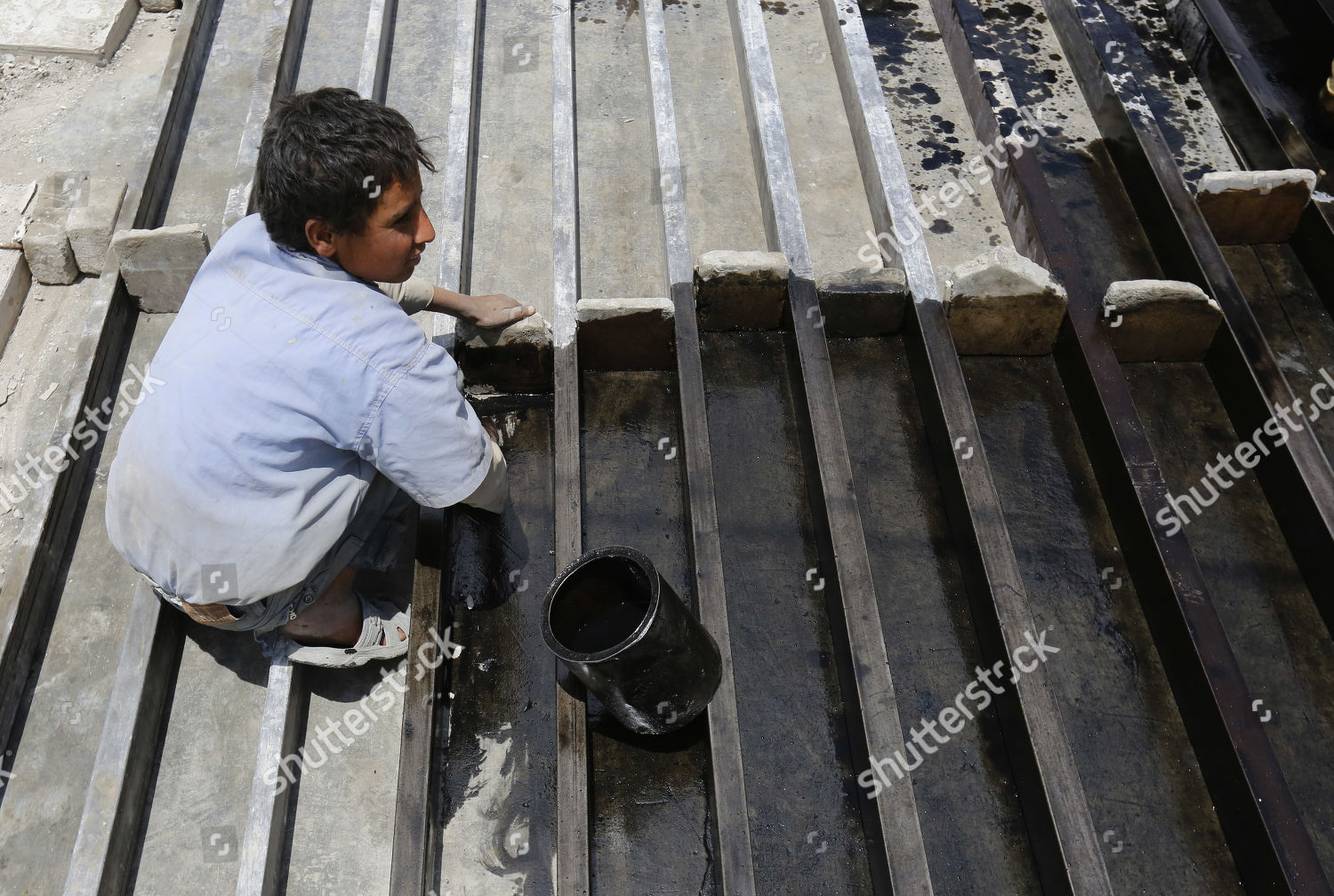 young Yemeni laborer cleans tiles moulds tile Editorial Stock Photo
