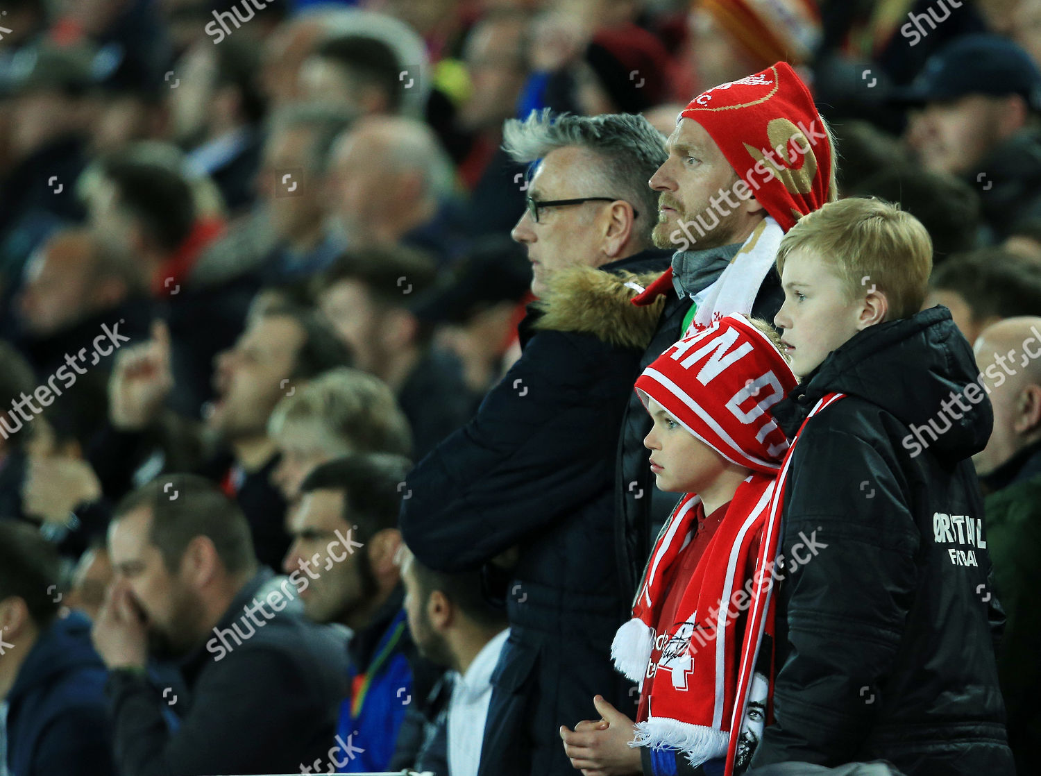 Liverpool fans wearing scarves over their heads Editorial