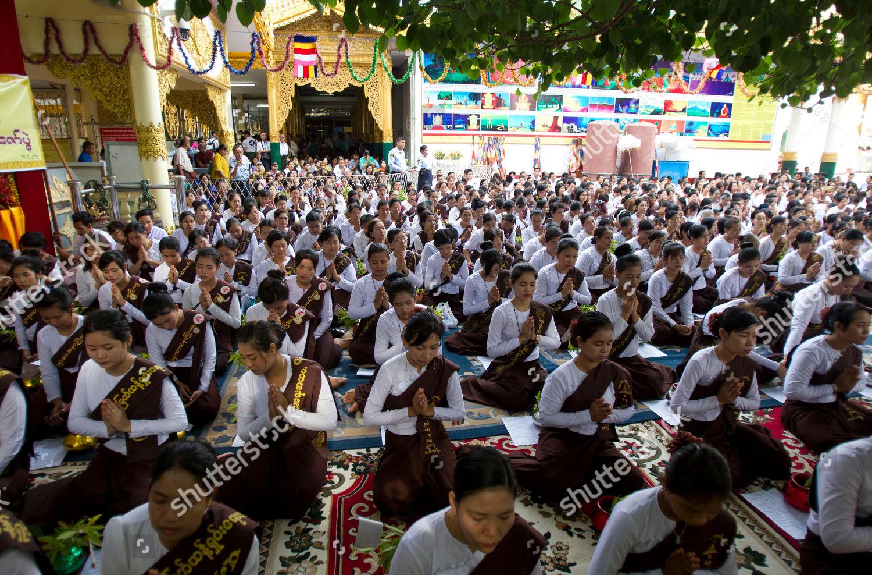 Buddhist devotees pray during religious ceremony mark
