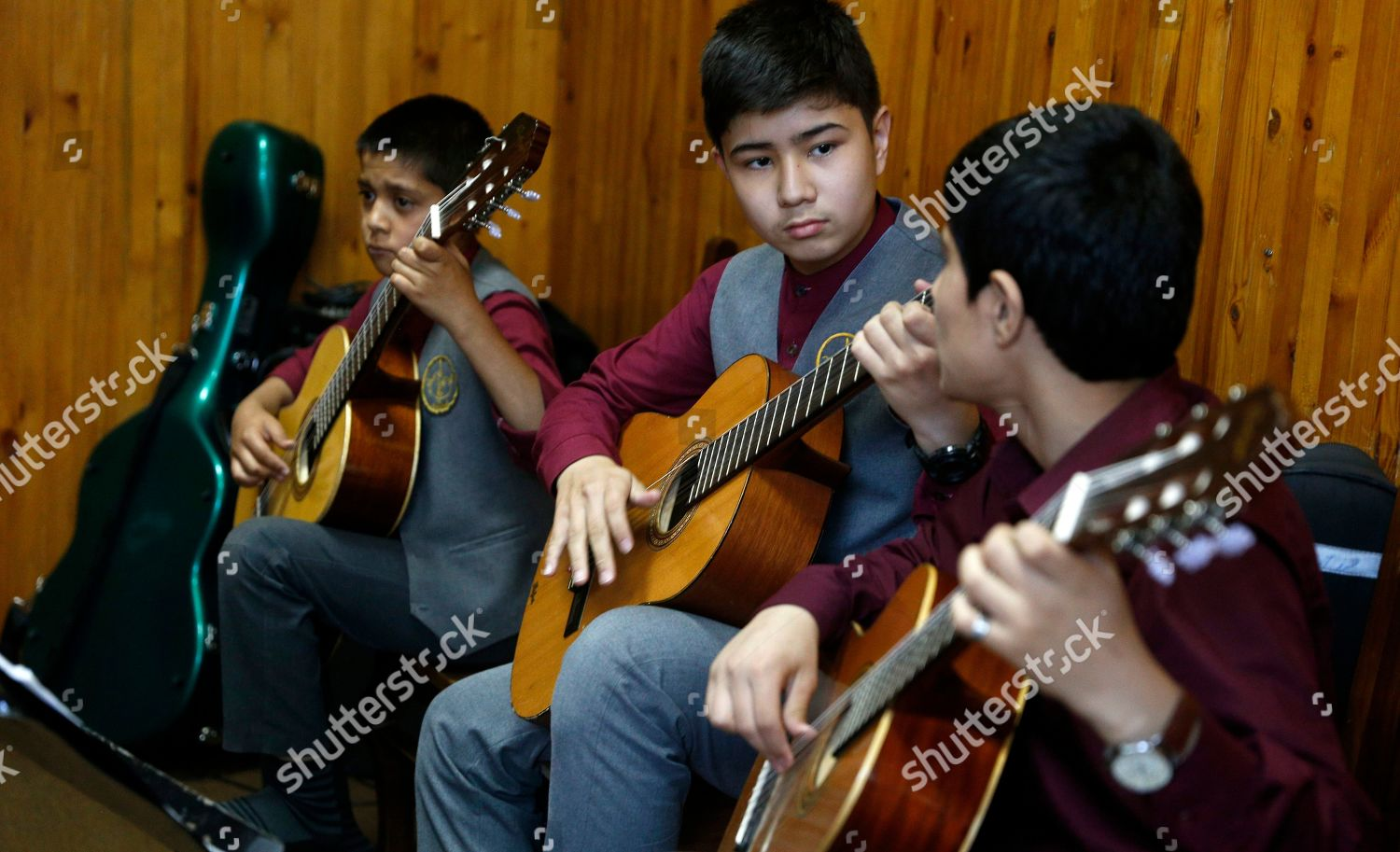 Afghan music students play guitar during practice Editorial