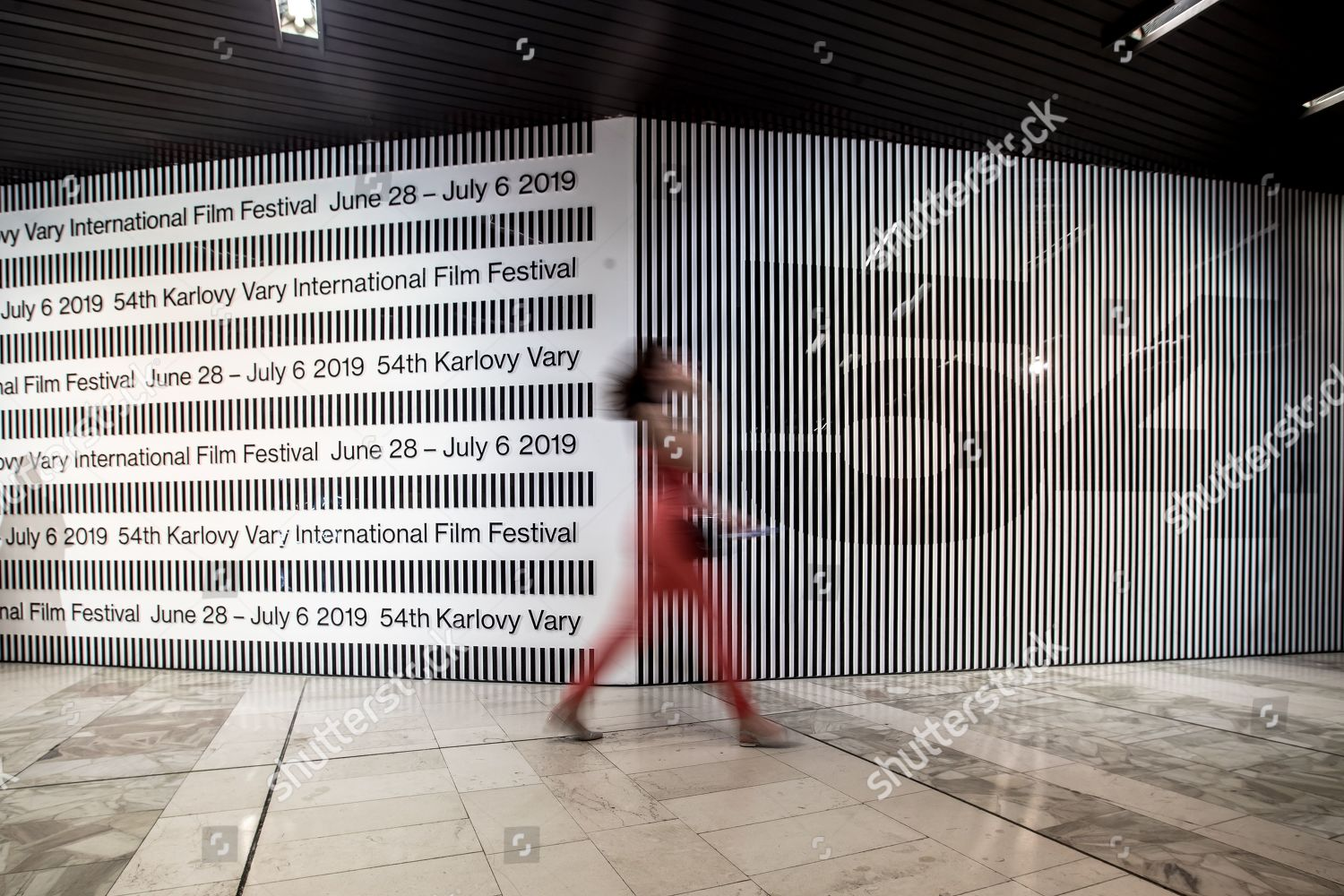 woman walks past wall festivals motive during Editorial Stock Photo