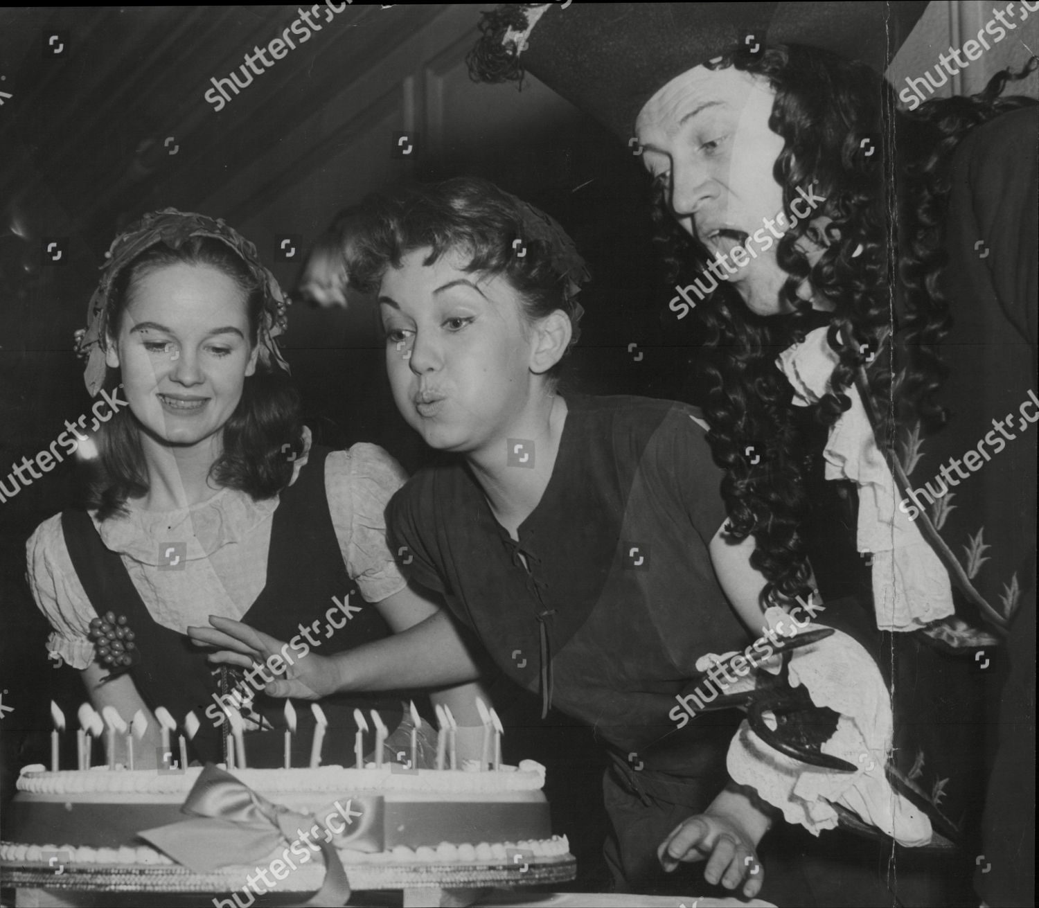 Stock photo of Actress Janette Scott As Peter Pan Blows Out Candles On Her Cake On Her 18th Birthday At Scala Theatre London With Actor John Mccallum As Captain Hook And Frances Guthrie As Wendy