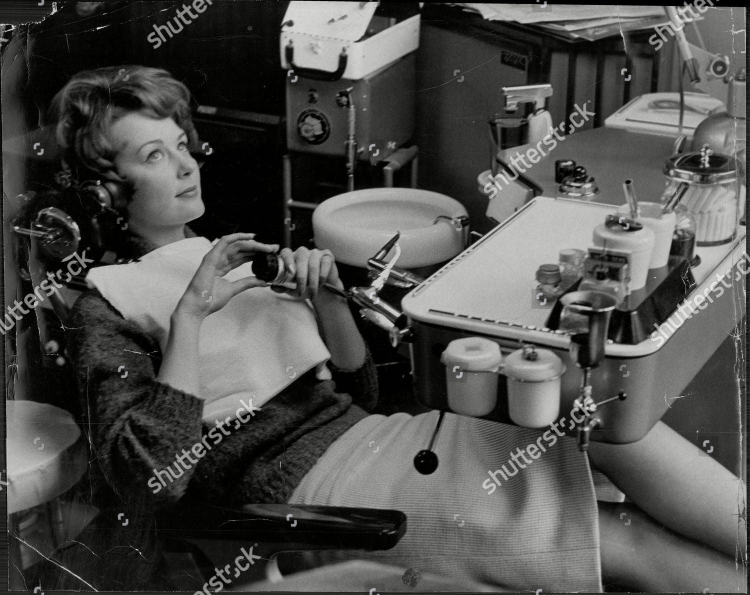 Stockfoto von Carol Bainbridge Model Listening To Music Through Headphones While In Dentist Chair To Distract Her From Operation 1960.