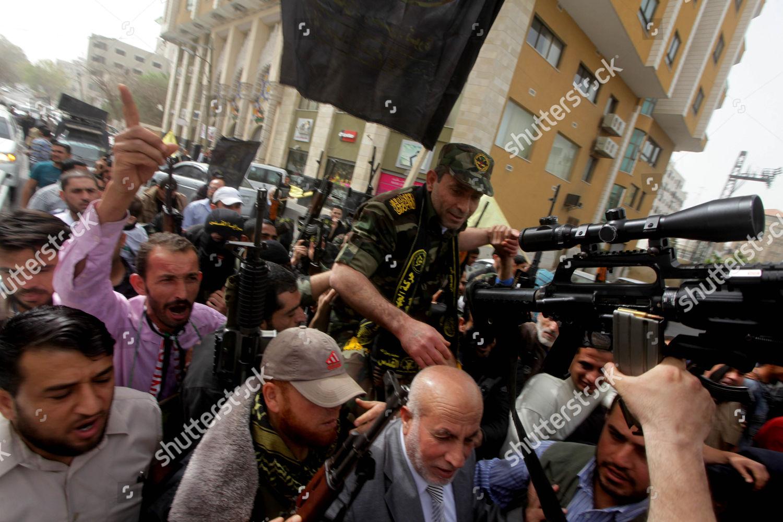 Ebrahim Barod holding assault rifle celebrates fellow