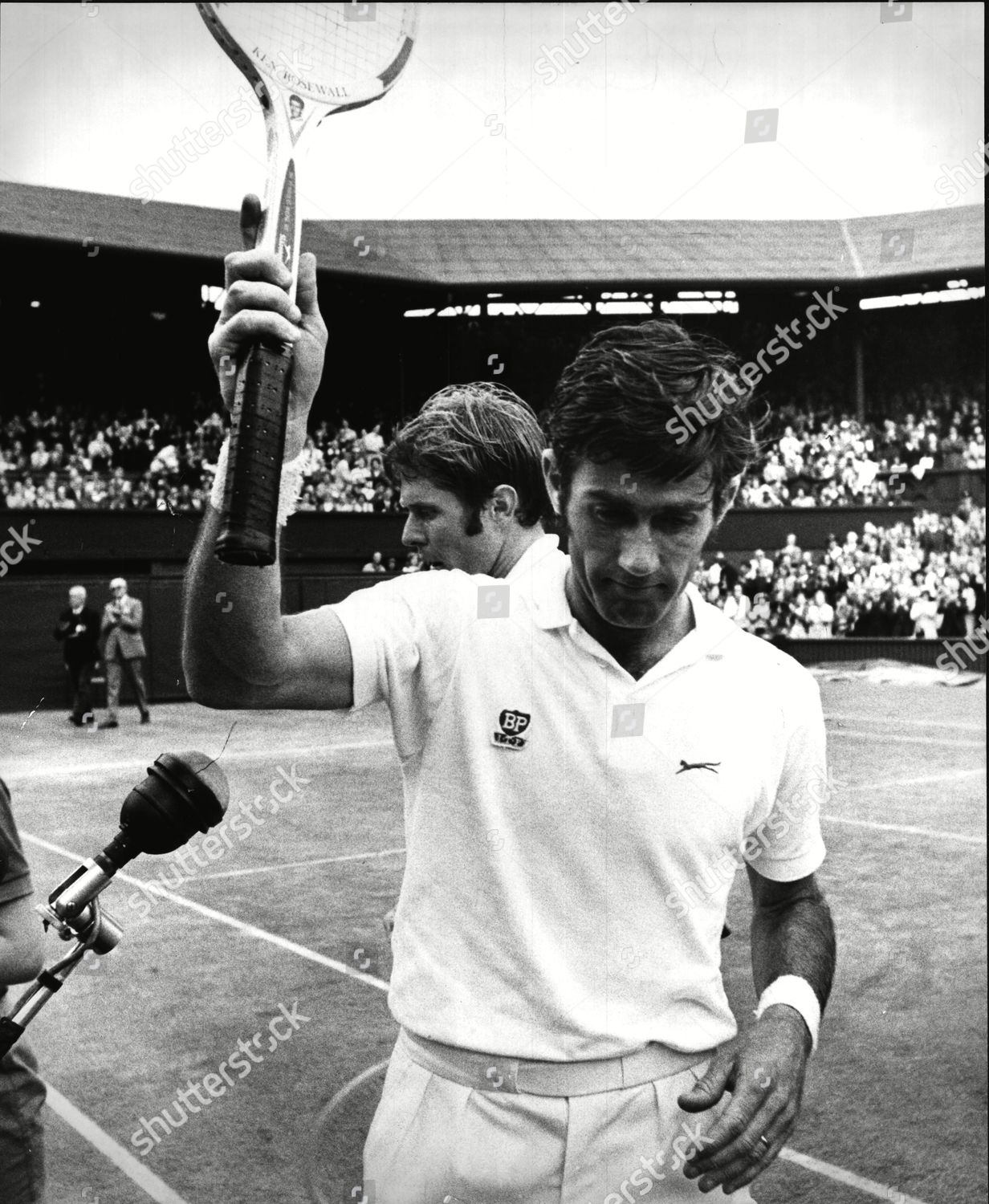 Stock photo of Ken Rosewall Raising His Racquet In The Air After Beating Opponent Cliff Richey At Wimbledon.