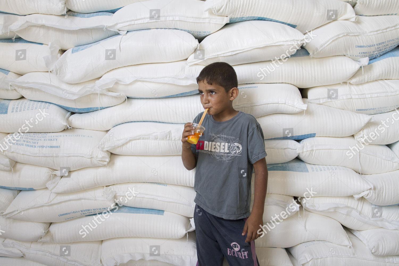 Palestinian child front flour sacks UNRWA food Editorial