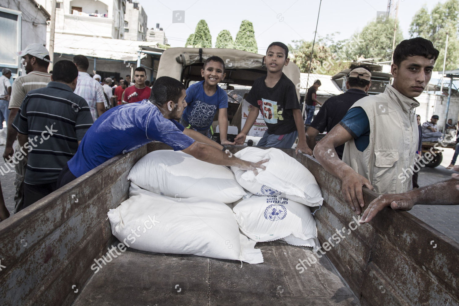 Palestinians collect food supplies flour sacks UNRWA