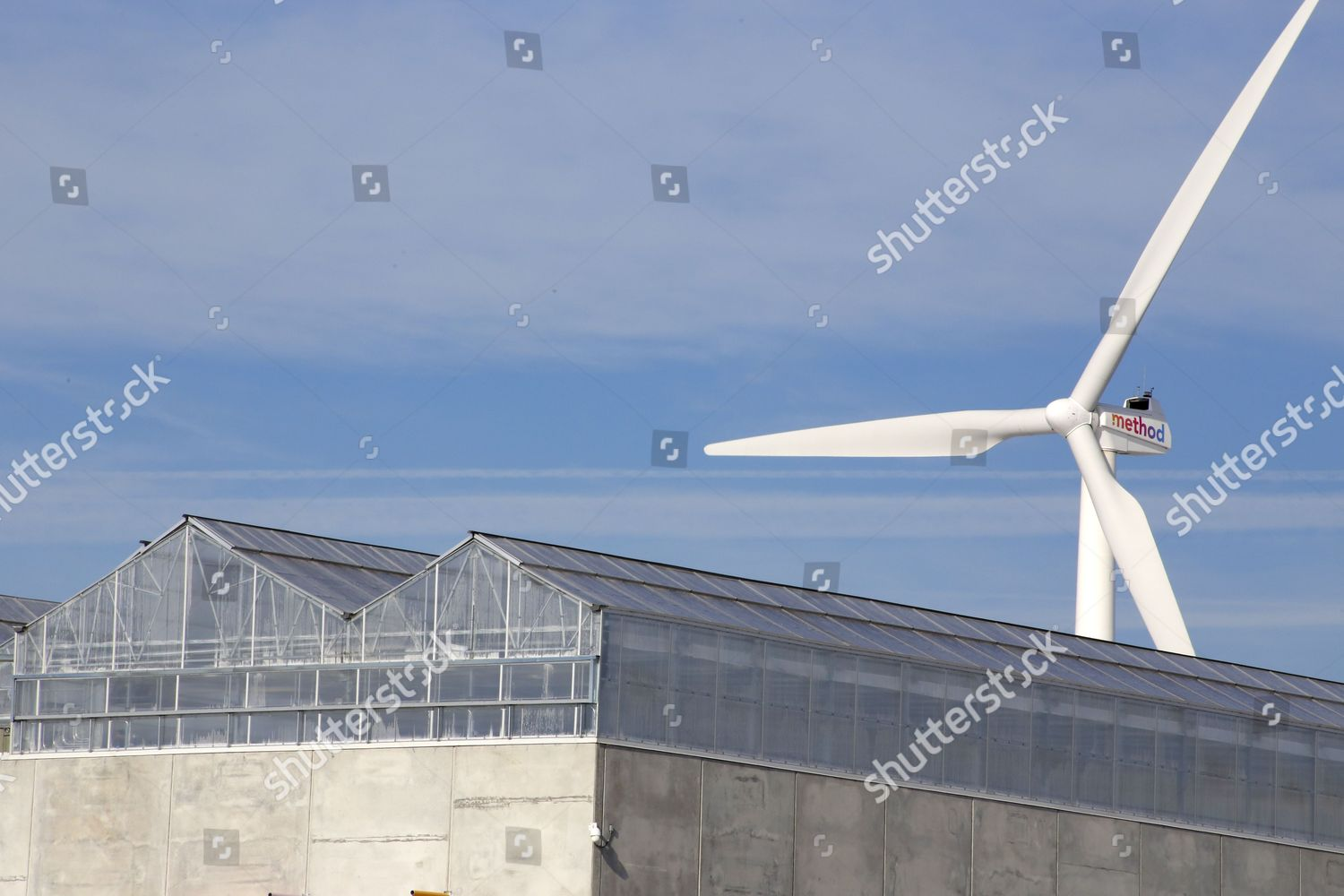 wind turbine twirls behind giant rooftop greenhouse