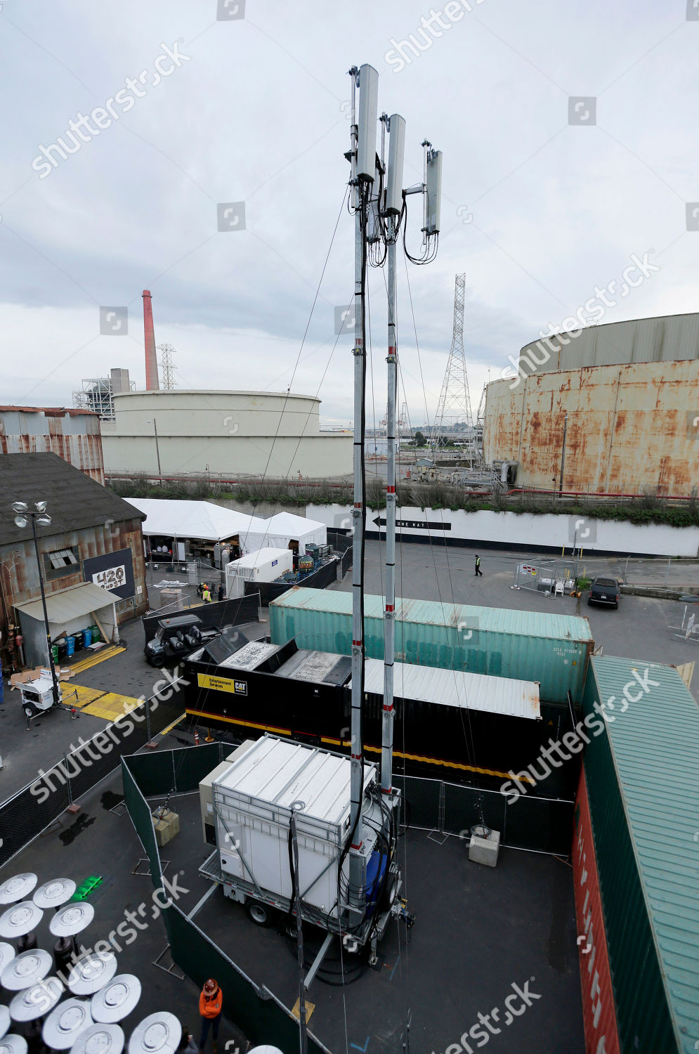 temporary cellular antenna rises alongside warehouse where Editorial