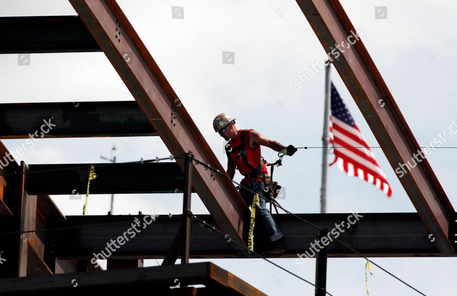 ironworker walks across beam on building under Editorial