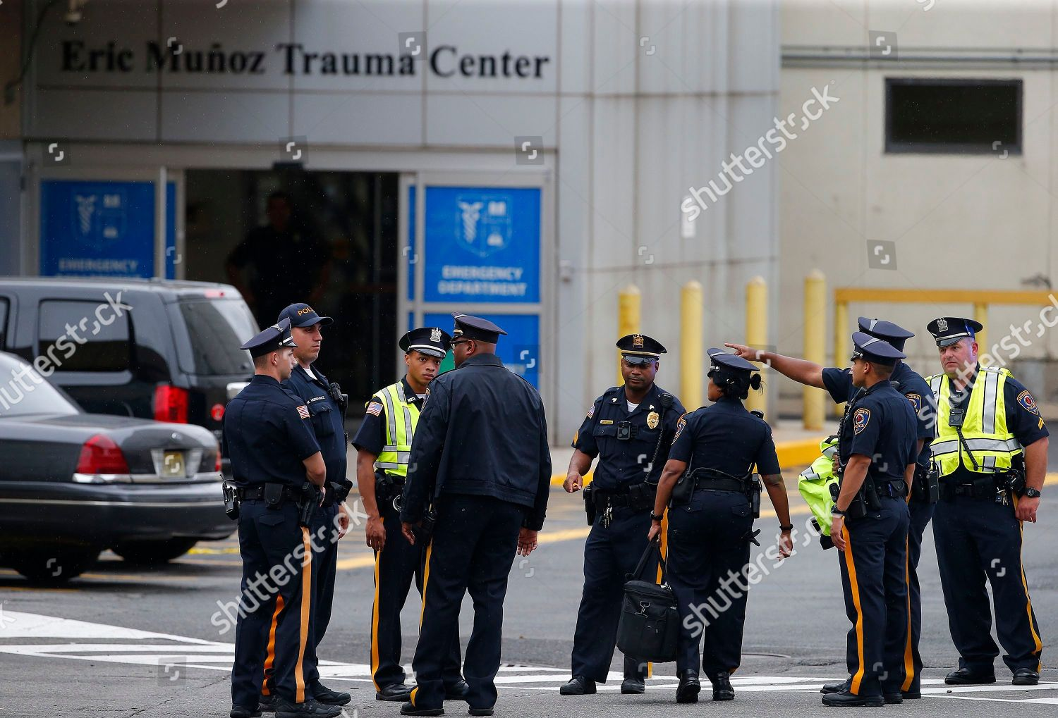 Police investigators gather outside University Hospital Newark