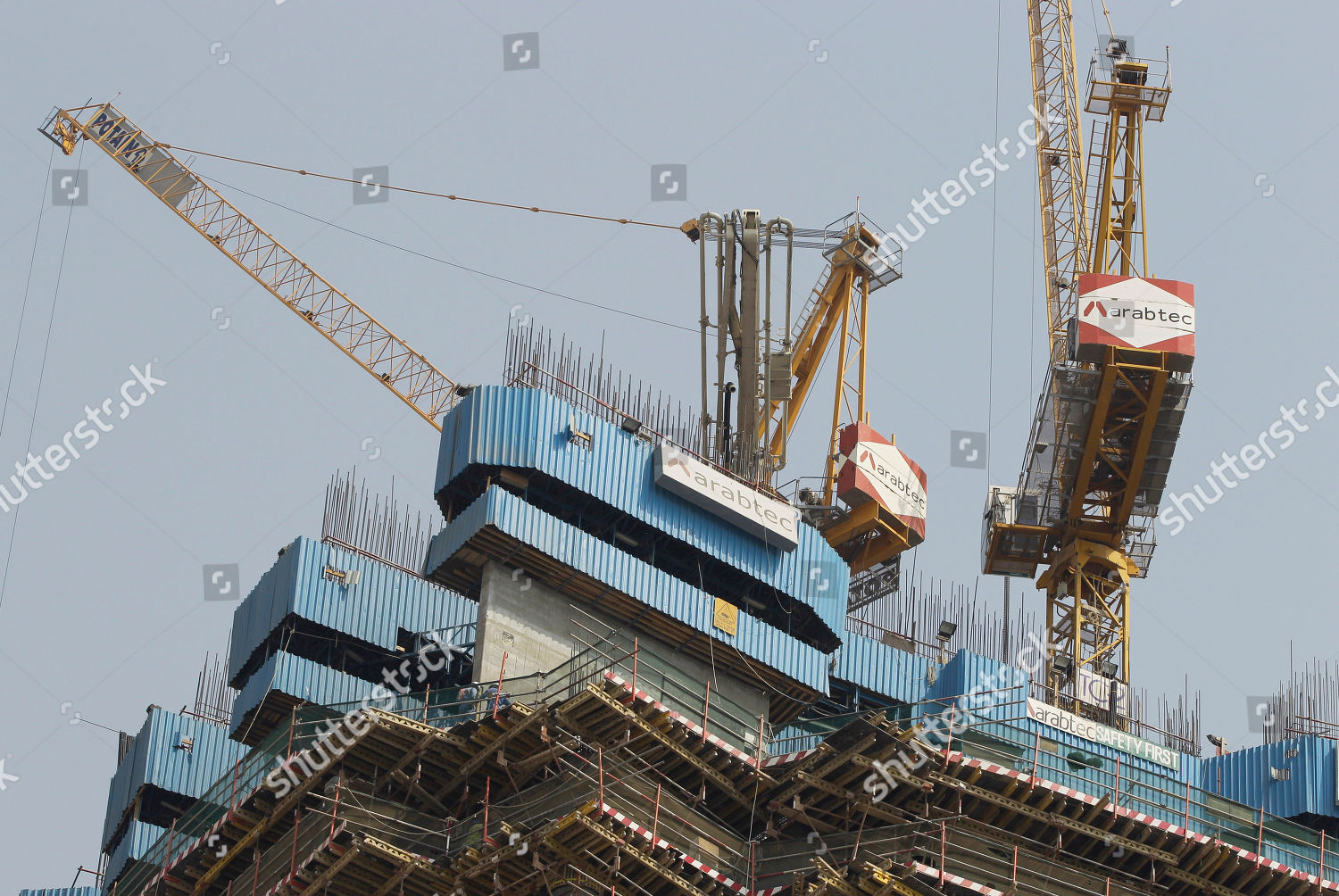 Workers operate cranes Arabtec construction company on Editorial