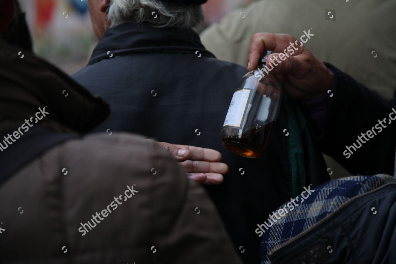 Men share drink before entering homeless shelter Editorial Stock