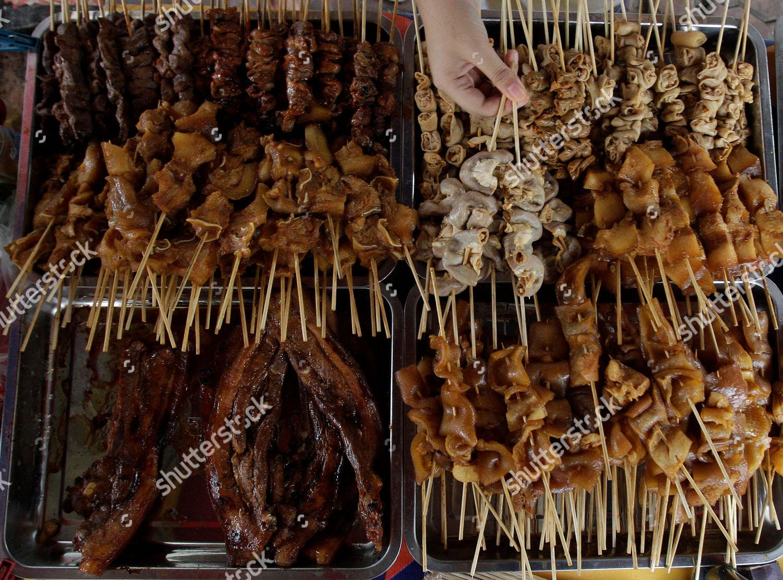 Filipino woman chooses among assortment barbecue delicacies