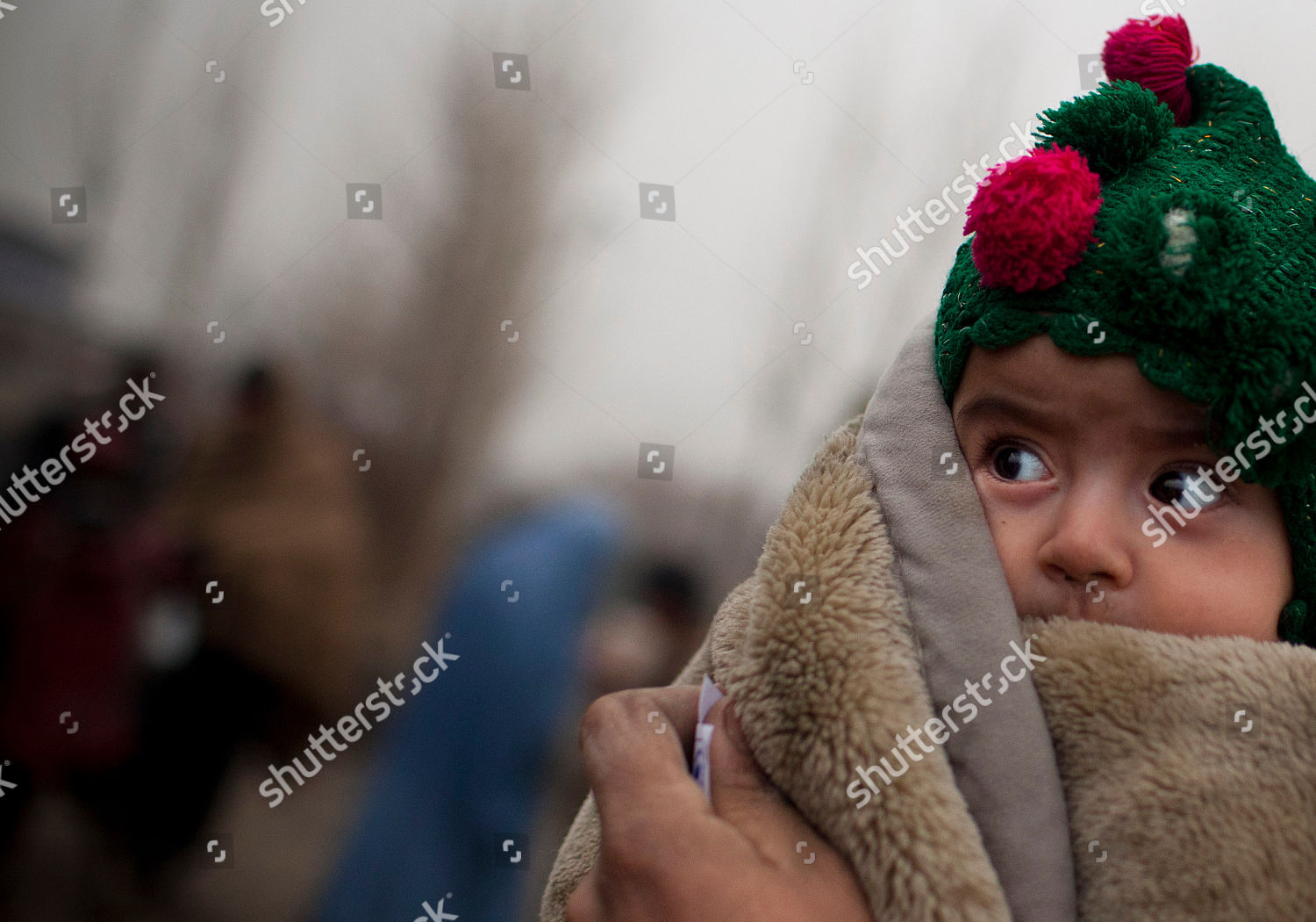 Afghan refugee child waits her father pick Editorial Stock Photo