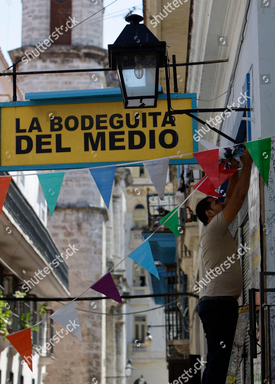 Worker Hangs Decorative Flags Outside Famous Restaurantbar