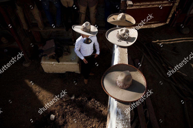 Mexican charro walks by sombrero hats during Stock Photo (6997025b ... f9708050ea4