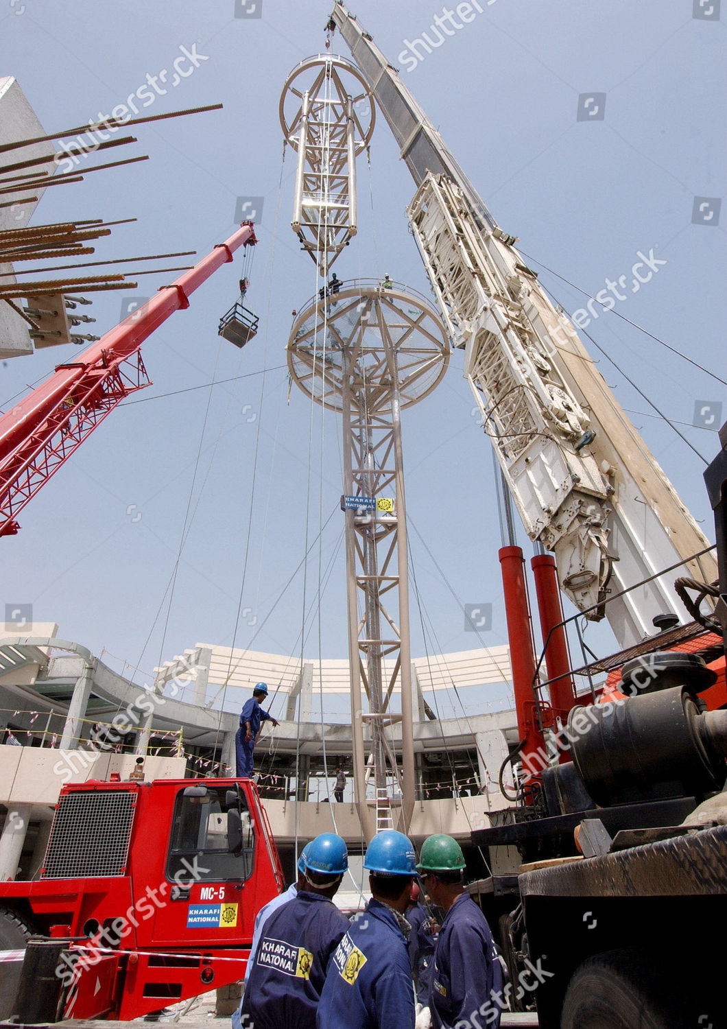 RICHESS Construction workers erect tower on seaside