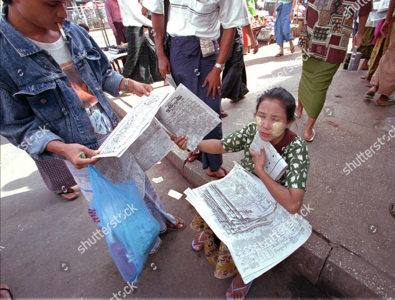 LOTTERY VENDOR Burmese lottery vendor sits on Foto editorial en