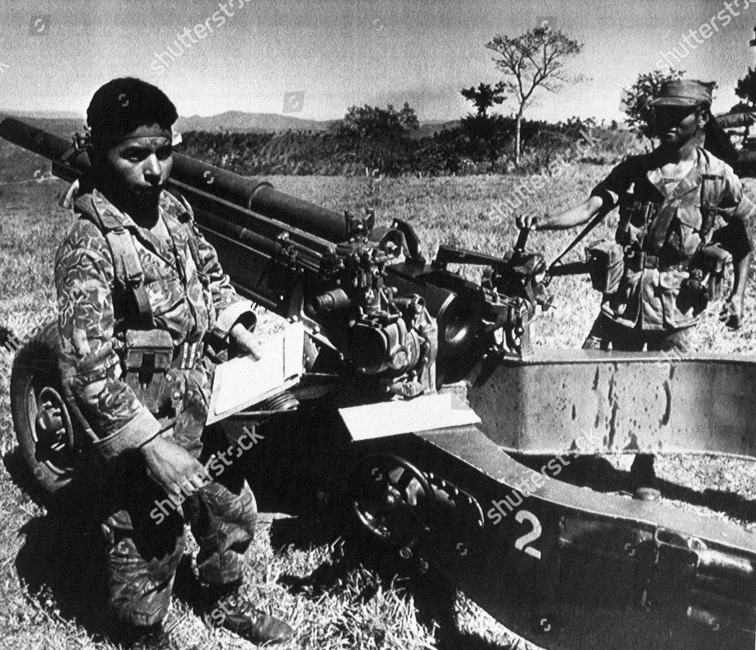 Two Salvadoran soldiers stand next 105mm Howitzer Editorial