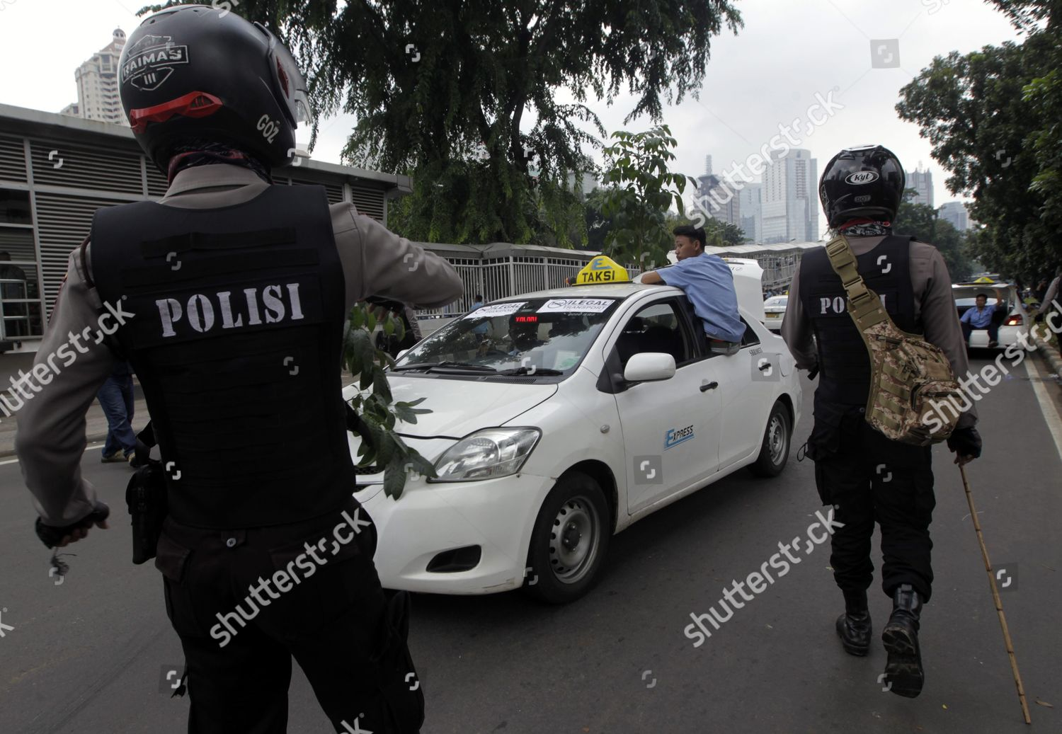 Indonesian Police Officers Curb Taxi Drivers During