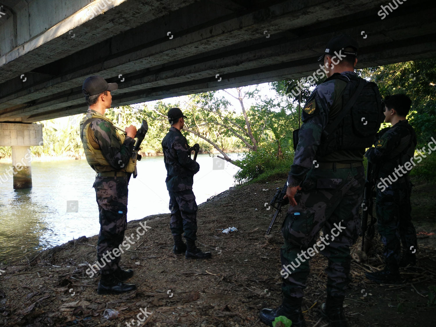 Filipino soldiers stand guard along river during Editorial