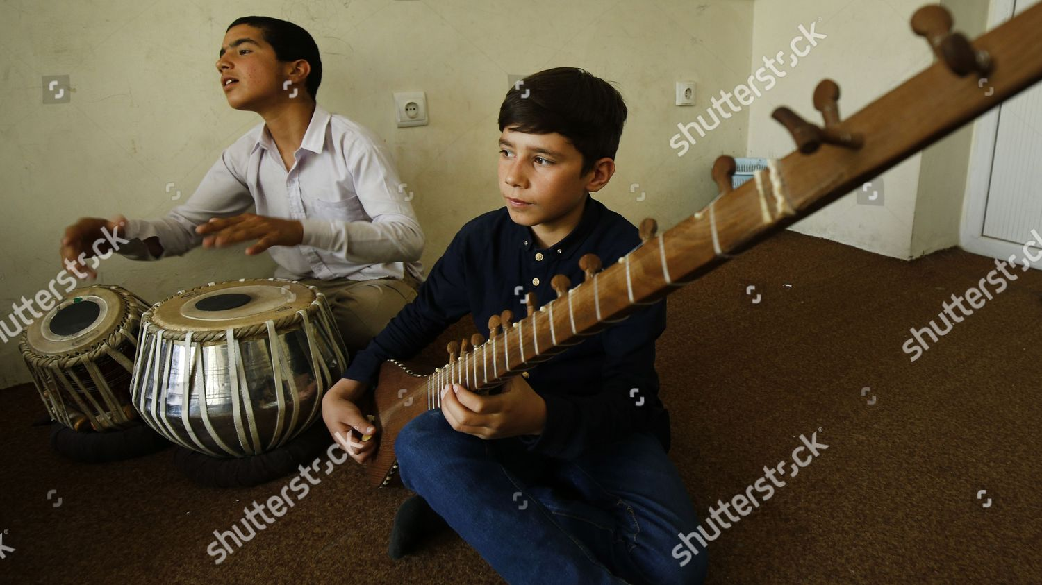 Afghan music students plays their instruments during