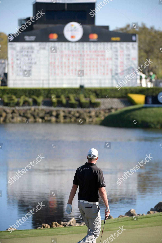 Marc Leishman Australia looks leaderboard while walking Foto