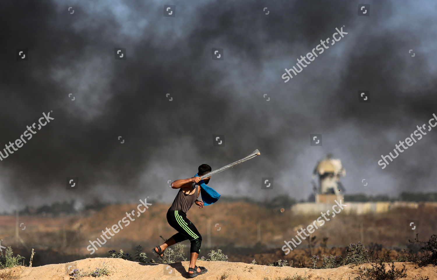 Palestinian protester uses slingshot hurl stones towards