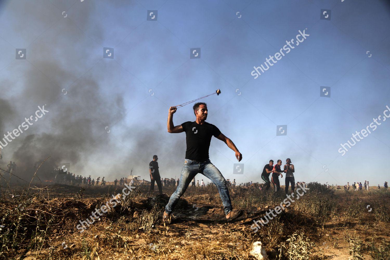 Palestinian protester uses slingshot hurl stones towards