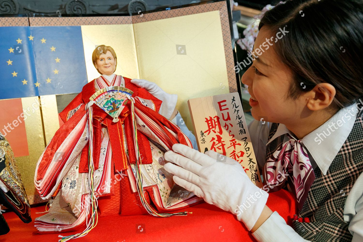 staff member displays Japanese hina doll modeled Editorial