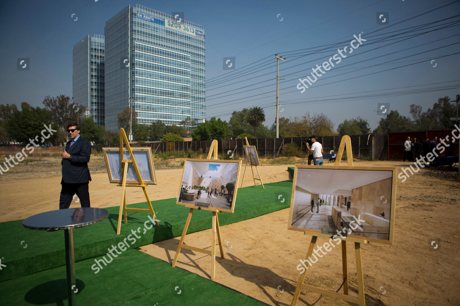 man walks past images depicting plans nearly Editorial Stock