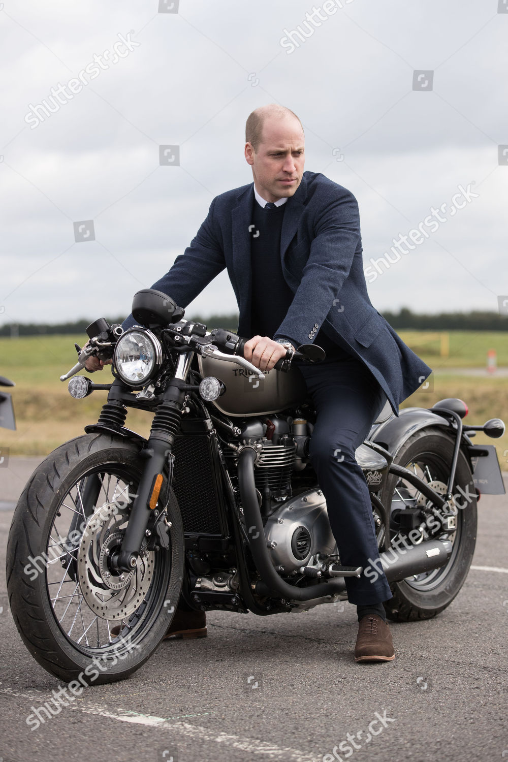 Prince William sits upon Triumph Bobber motorcycle Editorial Stock