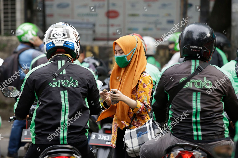 Indonesian woman pays GrabBike driver Jakarta Indonesia Editorial