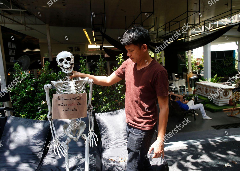 Thai employee decorates mock skeleton placard reading