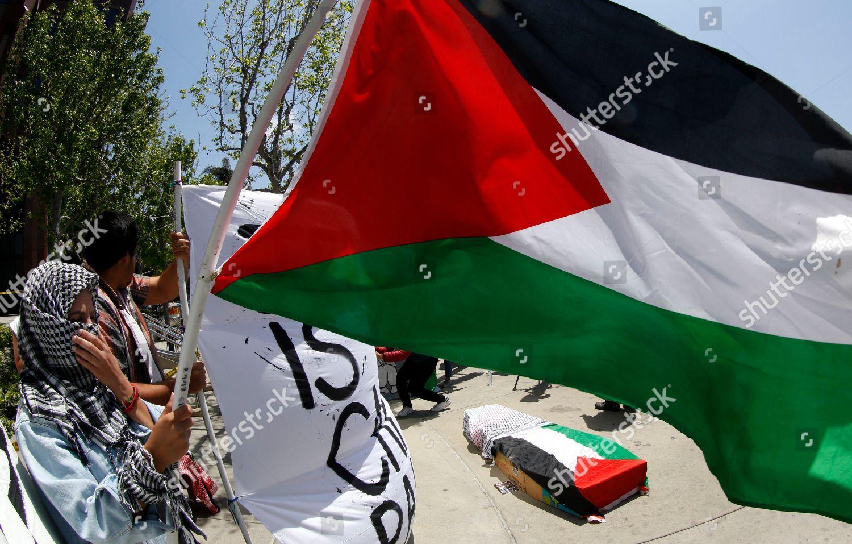 demonstrator holds Palestinian flag outside Israeli Consulate