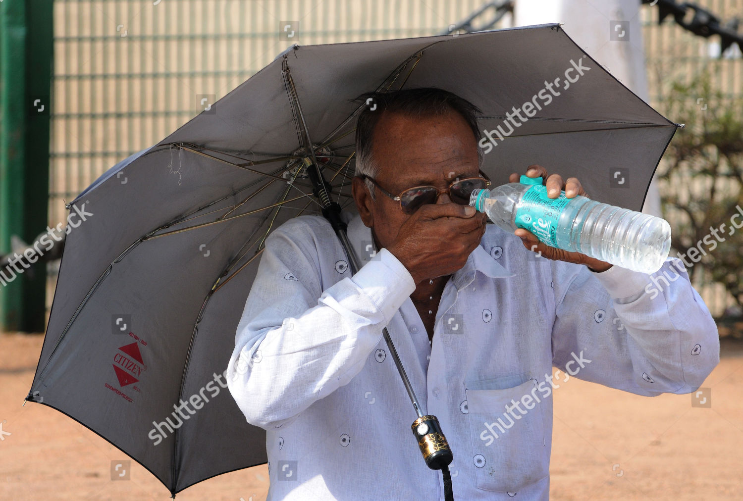 Indian man drinks water while holding umbrella Editorial Stock ...