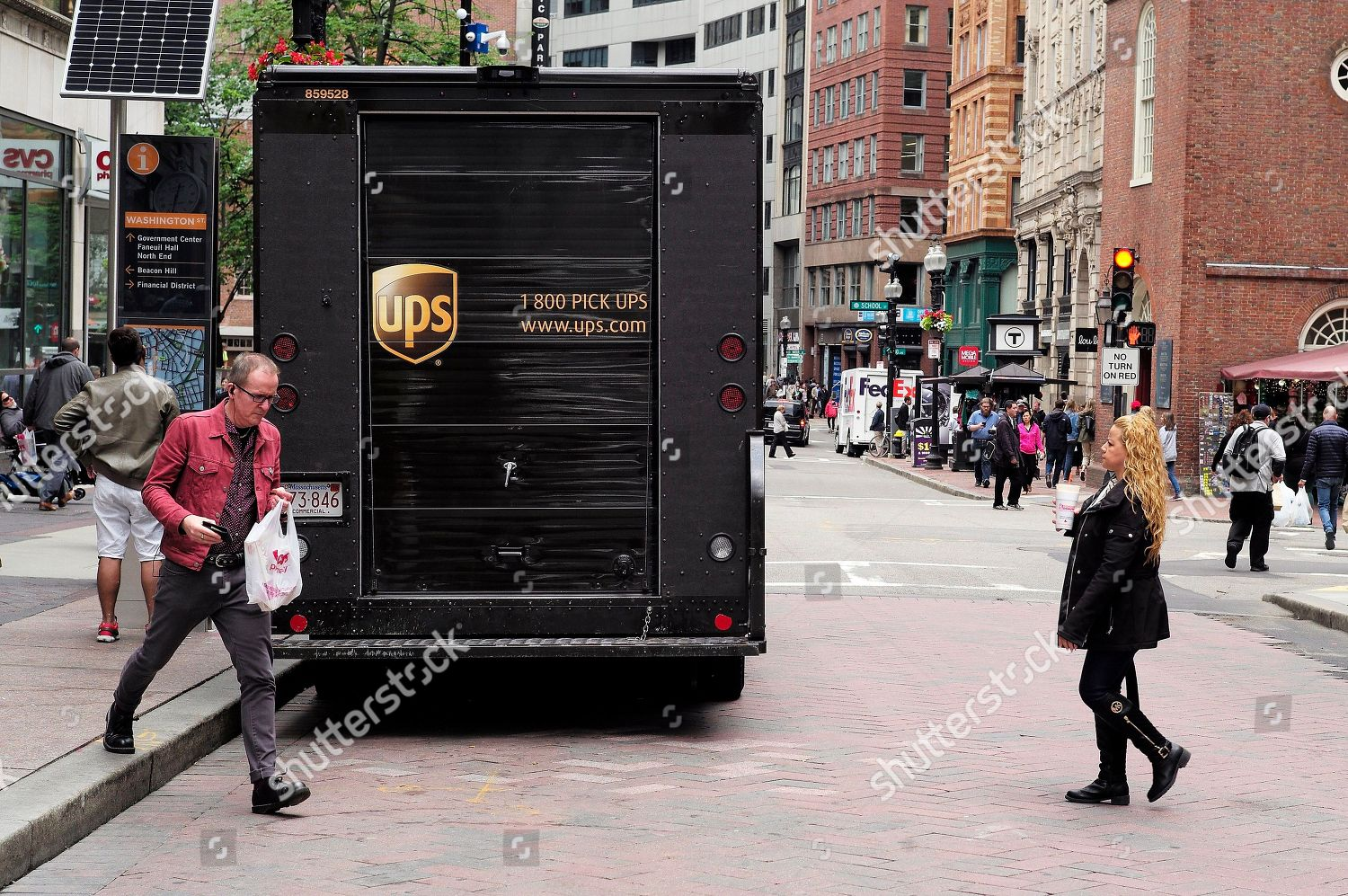 People walk past United Parcel Service UPS Editorial Stock