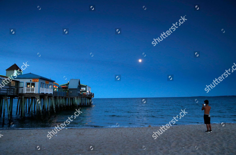 beachgoer pauses near Pier photograph moon rising Editorial Stock