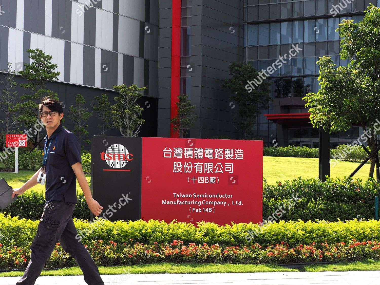 man walks past sign Taiwan Semiconductor Manufacturing Editorial
