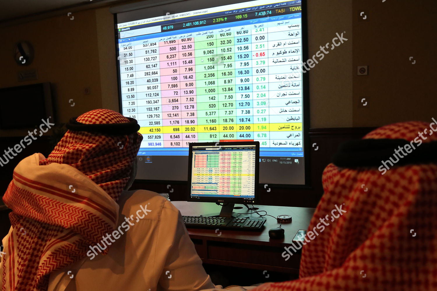 Saudi traders follow shares on screen stock Editorial Stock Photo