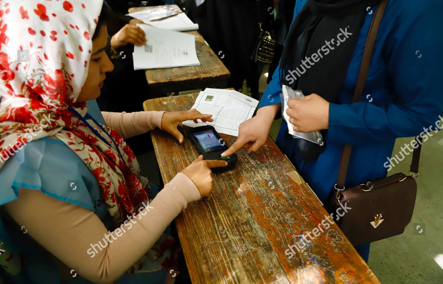 Afghan election worker takes fingerprint woman through