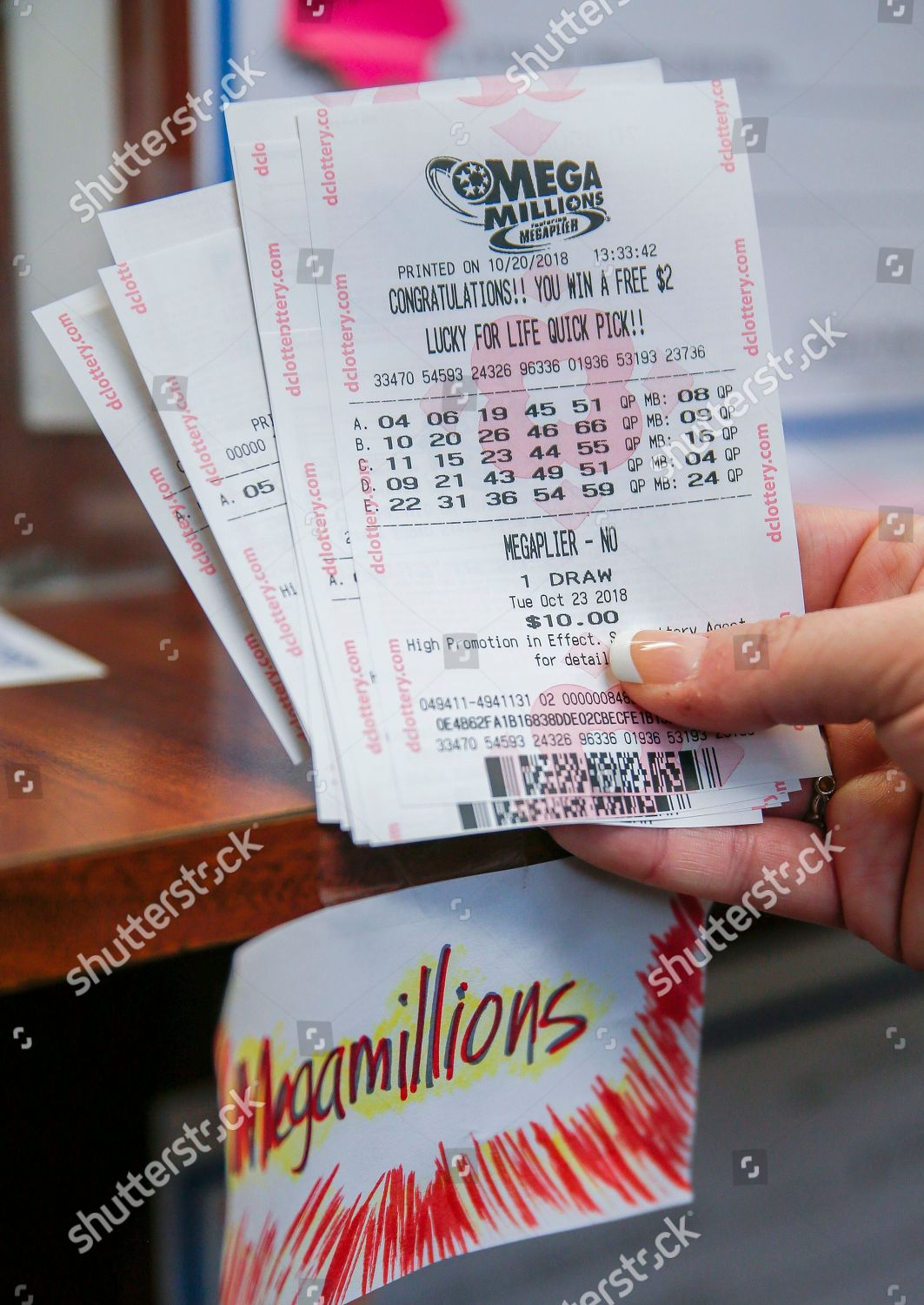 customer shows her purchased Mega Millions lottery Editorial